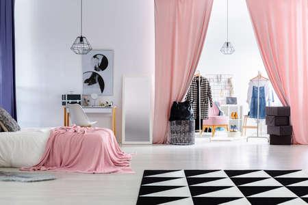 De slaapkamer van de aantrekkingskrachtvrouw met roze bekleding op bed en roze gordijnen in ingang aan garderobe
