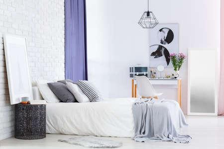Ontwerperstafel naast bed in de slaapkamer van de vrouw met bloemen en schoonheidsmiddelen op toilettafel