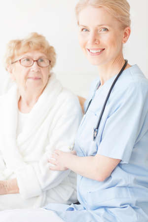Happy nurse in blue uniform sitting on hospital bed next to older woman in robe