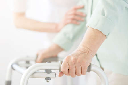 Nurse in white uniform supporting elderly person using a walker at nursing home