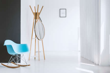 Minimalist white hall of modern apartment with blue rocking chair standing near a black contrasting wall