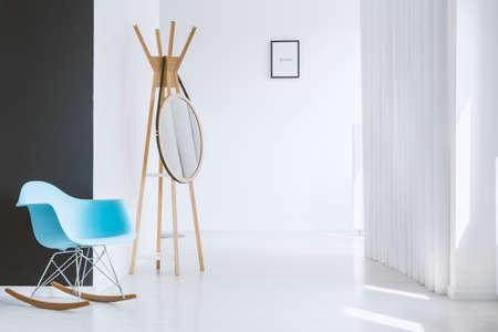 Unbedeutende weiße Halle der modernen Wohnung mit dem blauen Schaukelstuhl, der nahe einer schwarzen kontrastierenden Wand steht Standard-Bild - 87763554