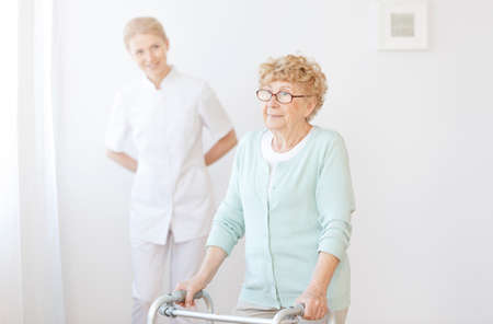Smiling caregiver taking care of elderly woman using a walker in bright nursing home