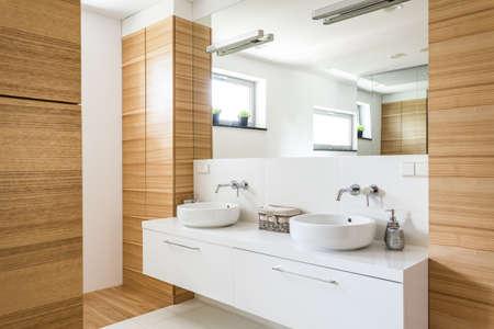 Salle de bain élégante avec deux lavabos, miroir et design en bois Banque d'images