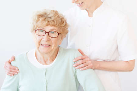 Smiling assistant in white uniform hugging old lady in mint sweater during meeting at home