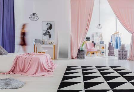 Driehoekstapijt in de slaapkamerbinnenland van de vrouw met roze gordijnen in ingang aan kleedkamer