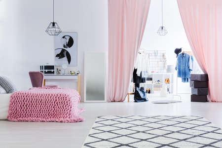 Zwart-wit poster boven kaptafel in de slaapkamer van de vrouw met glamour walk-in closet