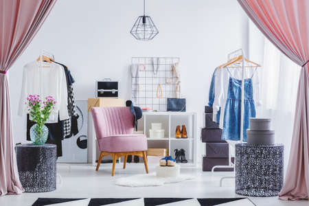 Pink chair in dressing room with flowers on designer table and clothes on hangers. Fashionable dressing room concept Stok Fotoğraf - 87806767