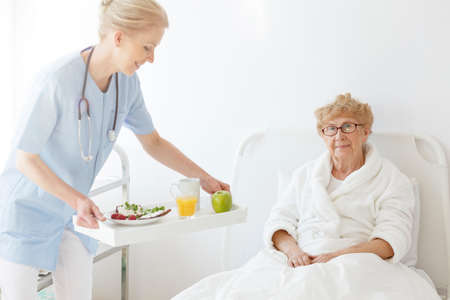 Friendly doctor bringing tasty and healthy food to disabled senior woman in white robe