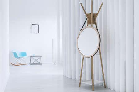 거울과 나무 옷걸이가있는 현대 홀의 끝에 흰 벽이있는 밝은 거실