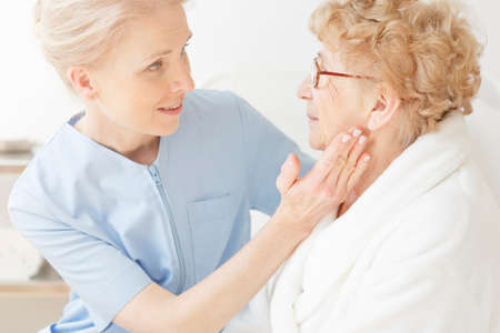 Friendly nurse sitting next to elderly woman, comforting her before surgery at hospital