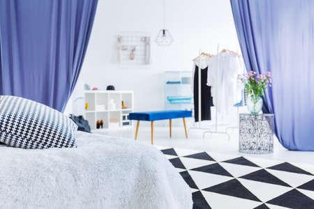 De slaapkamer van de aantrekkingskrachtvrouw met bloemen op lijst in ingang aan kast met blauwe kruk en gordijnen