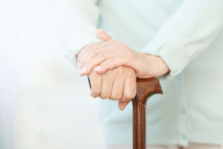Senior person holding hands on wooden cane during stay in nursing home
