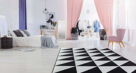 Zwart en wit tapijt en roze stoel in het interieur van de ruime vrouwenslaapkamer met kleedkamer