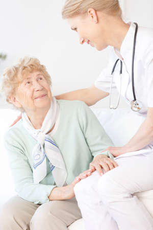 Senior woman talking to doctor in white uniform with stethoscope while sitting in common room