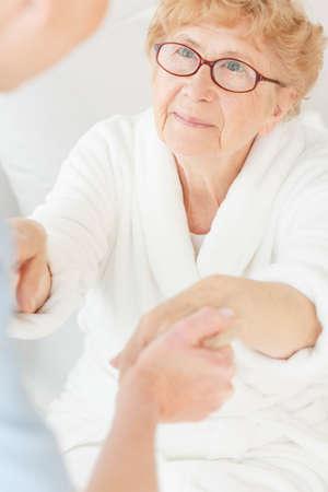 白いローブの高齢患者のベッドから起きるのを助ける看護師 写真素材