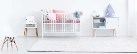 Big white carpet in the bright baby room with decorative cushions and chair Stock Photo