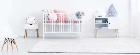 Groot wit tapijt in de heldere babyruimte met decoratieve kussens en stoel Stockfoto