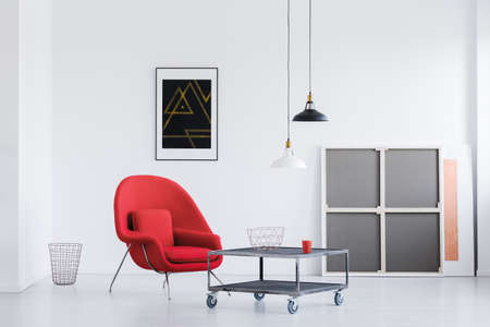 Two black and white lampshades hanging in bright living room with wheeled table and red armchair Stock Photo