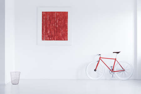 Metal basket placed in the corner of white room with red poster and bike