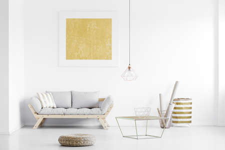 Golden poster hanging on white wall above wooden couch in bright living room with footrest and baskets