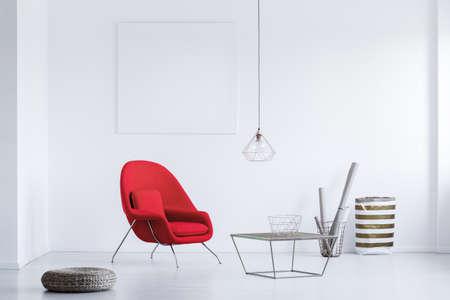 Ronde rieten voetsteun geplaatst op de vloer naast rode leunstoel in witte wachtkamer met industriële tafel en lampenkap