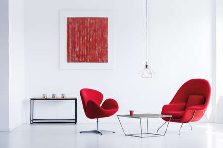 Black metal table with three candles standing in the corner of white room with red armchairs