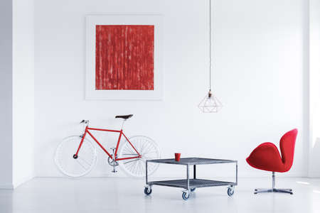 Red glass standing on metal table with wheels in white room with poster Stock Photo
