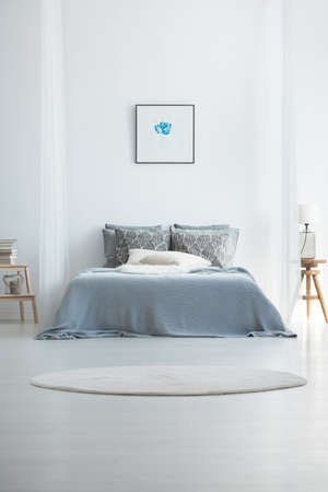 Round white carpet in cold bedroom interior with king-size bed against the wall with picture