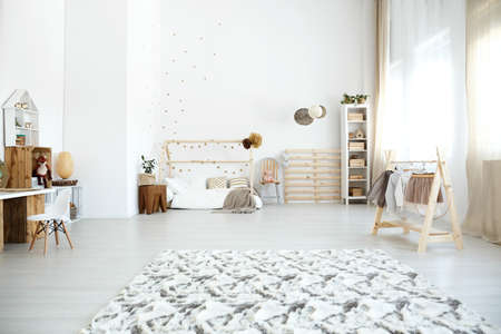Patterned carpet in spacious multifunctional girls room with clothes on handmade rack and DIY bed