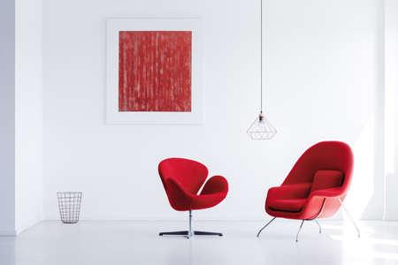 Twee comfortabele rode fauteuils geplaatst in lichte kamer met abstracte schilderkunst en prullenbak