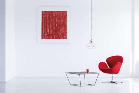 Rode ceramische koffiemok die zich op de metaallijst naast moderne leunstoel bevindt