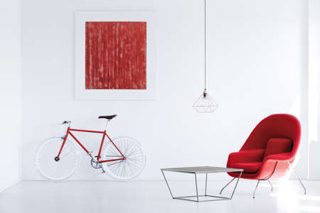 Het rode moderne affiche hangen op de muur boven fiets in ruimte met industriële lijst