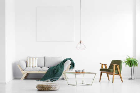 Dark green blanket thrown on grey sofa in bright living room with empty poster and armchair Фото со стока - 89250611