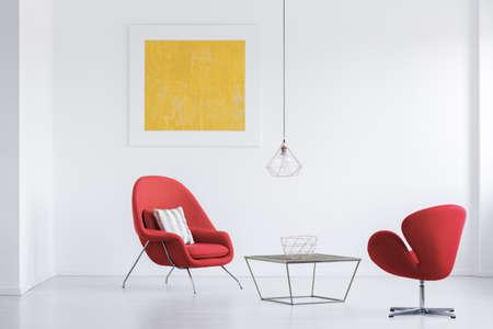 Handgemaakte mand geplaatst op de tafel staan onder koperen lampenkap in witte kamer met rode fauteuils Stockfoto