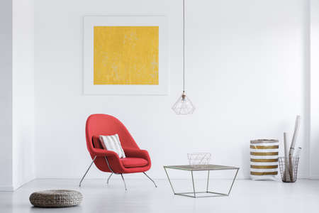 White room with yellow poster and two baskets in the corner Stock Photo