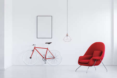 Red and white hipster bicycle standing in white room with comfy armchair and mockup poster