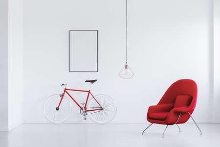 Rode en witte hipsterfiets die zich in witte ruimte met op zijn gemak leunstoel en modelaffiche bevinden Stockfoto