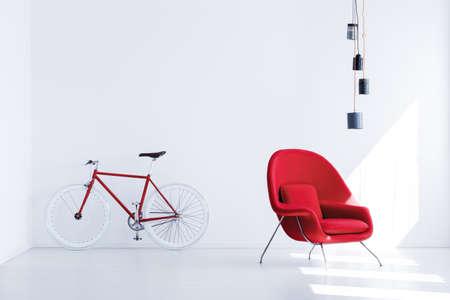Witte en rode fiets staande in eenvoudige wachtkamer met handgemaakte kan lampenkap