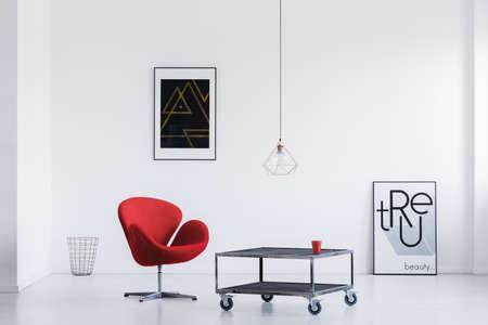 Stijlvolle wachtkamer met witte muren, industriële tafel, rode fauteuil en moderne posters