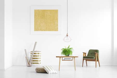 Papierrollen in metalen mand en groene fauteuil in witte kamer met gele poster
