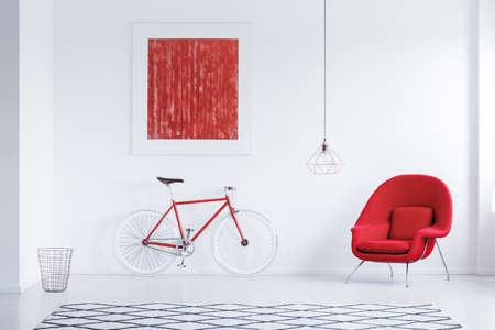 Red cycle in white room with carpet with geometric pattern, armchair and poster