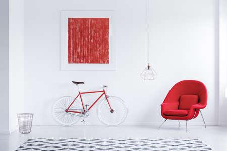 Rode cyclus in witte ruimte met tapijt met geometrisch patroon, leunstoel en affiche Stockfoto - 89250689