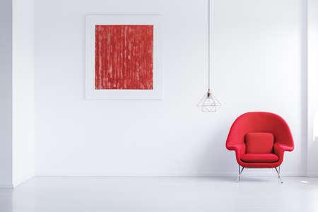 Eenvoudige lege ruimte met abstracte poster, rode leunstoel en koperen lampenkap Stockfoto