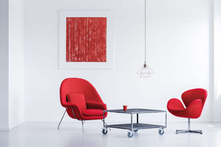 White simple waiting room with two red chairs by the industrial table