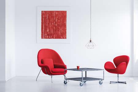 Witte eenvoudige wachtkamer met twee rode stoelen door de industriële tafel Stockfoto