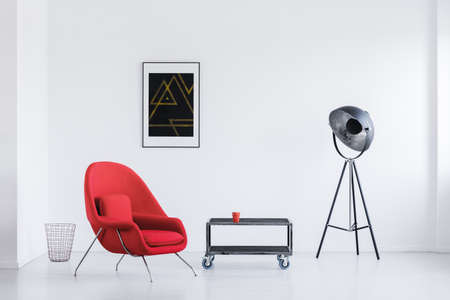 Big studio lamp in day room with red armchair and industrial table with wheels
