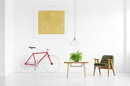 Groene ingemaakte installatie op houten lijst die zich naast leunstoel in heldere ruimte met fiets bevinden Stockfoto - 89277093