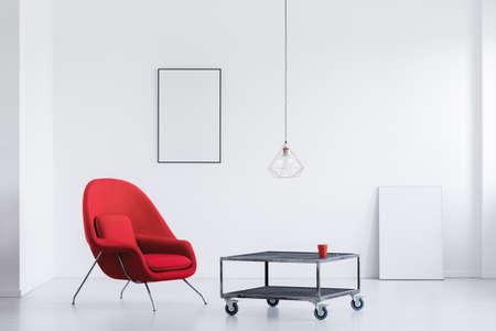 Witte kamer met metalen tafel, rode fauteuil en twee mockup-posters Stockfoto