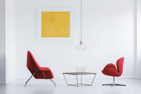 Modern red armchairs standing by the table with metal bowl in white interior Stock Photo